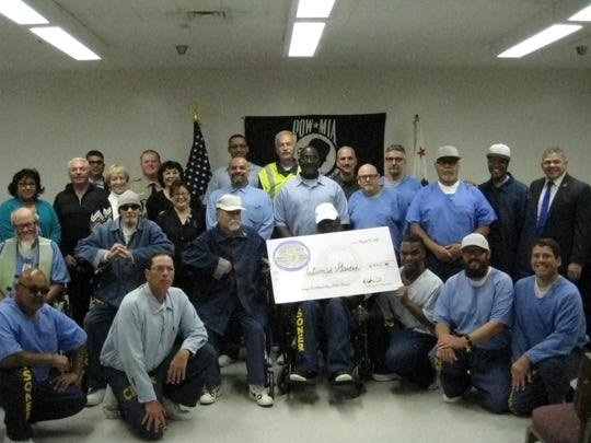 Inmates held a small ceremony to deliver their check to Tatum's Garden.