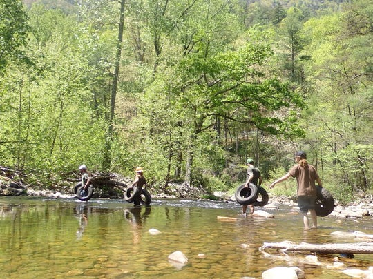 From left, volunteers Mike Jones, Jonathan Massey, Jake Hansen, and Nicholas Massey fording the Linville River as they relay trash on its long journey out of the wilderness.