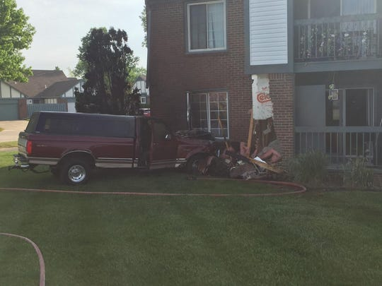 A head-on collision caused a pickup truck to veer off the road and into a condominium development.