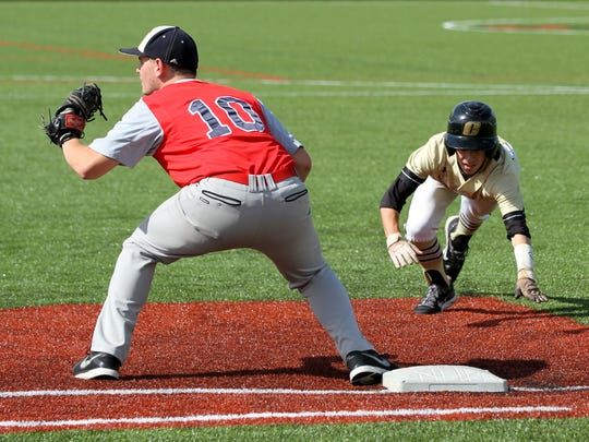 Corning's Brendan Walker dives back to first as Ketcham's Stephen Merrill awaits a pickoff throw during Saturday's Class AA state quarterfinal at Corning Community College.