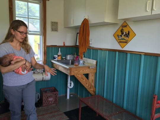 Emily Heizer Hall, holding her daughter, shows the goat milking room at Razzbourne Farms.