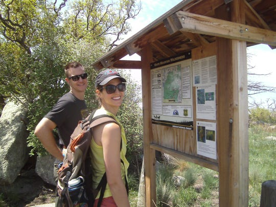 Sam and Meg, keen hikers from Oklahoma, check out the Monjeau Trailhead sign of Crest Trail  No. 25.