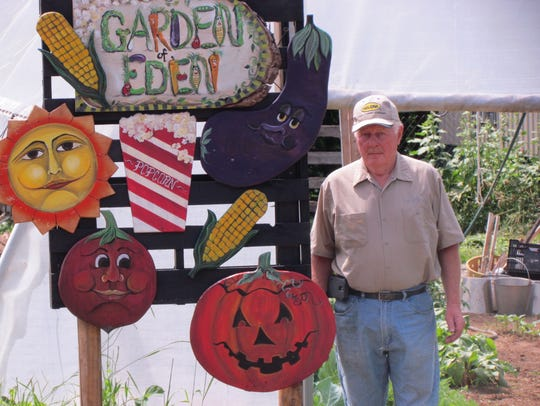 Wayne Hass poses with his Garden of Eden signage.