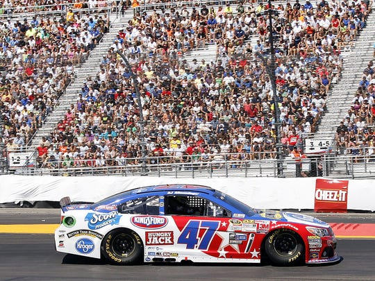 AJ Allmendinger drives past packed grandstands at Watkins