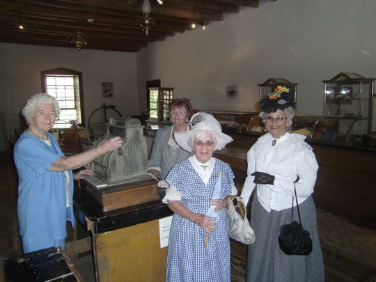 Tunstall Museum Volunteer Margaret, far left, gets into the spirit of shopping a hundred years ago with Cameo Ladies, l-r: Miss April, Miss Caroline and Miss Sunny.