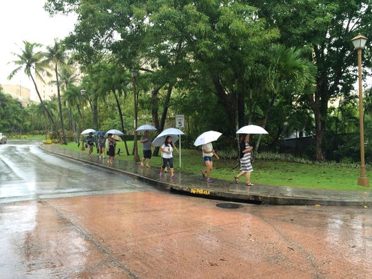 In this foto taken Aug. 4 in Tumon in front of the Hyatt Regency Guam, visitors shelter from heavy rain under umbrellas. Residents can expect more rain next week.