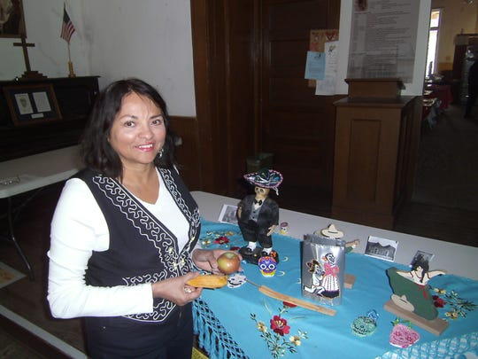 """Let's include an apple for the teacher and a tamal,""  Dr. Cynthia Orozco said as she creates an ofrenda, or altar, for Juan Patrón, ""Lincoln County's first teacher"" as well as a prominent Territorial New Mexican during Lincoln's Día de los Muertos."