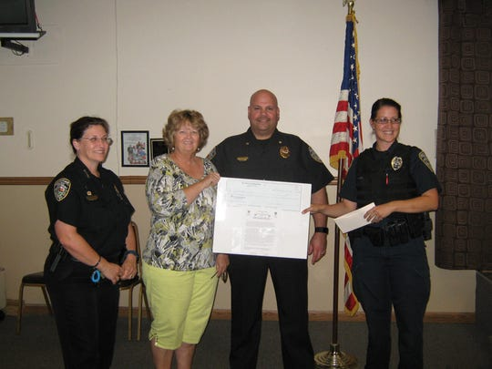 """EL-DOEs Vice President Debbie Davis presents a check for $1,000 to Chief Michelle Morris, Commander Dan Acosta and Officer Ashley Penn for the Sebastian Police Department's """"Shop With a Cop"""" program."""