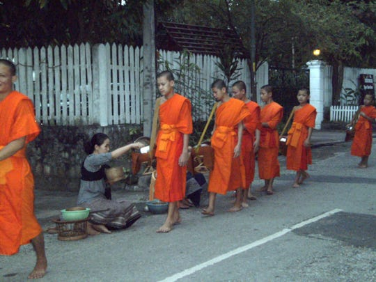 Orange-robed Buddhist monks receive alms from townsfolk in exchange for good karma.