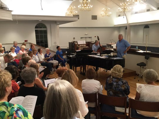 Music director Doug Renfroe leads Voices of Naples through a rehearsal. They perform this weekend.