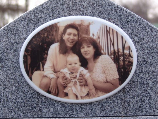A photo of Bruce and Carolyn Berman and their child on the back of Bruce's grave in Rahway.