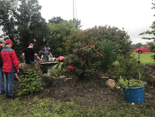 Students are pictured maintaining the rose bed at the