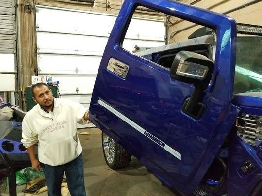 Minor Customs LLC administrative assistant Julian Garcia shows a custom door for a Hummer truck.