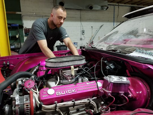 Lead auto body technician Brian Valle works on a 1973 Buick Centurion.