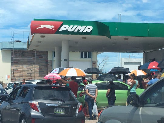 Drivers and pedestrians swarm a gas station in Bayamon,