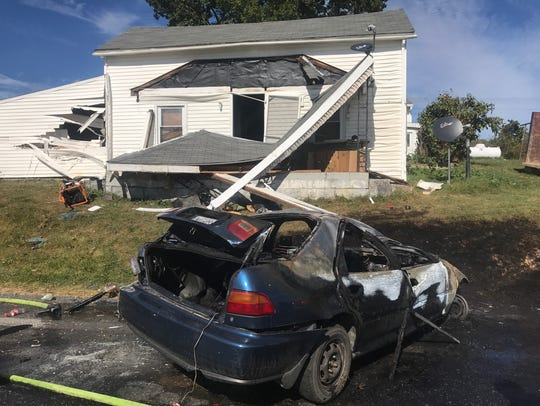 The damaged house and car after a one-vehicle wreck