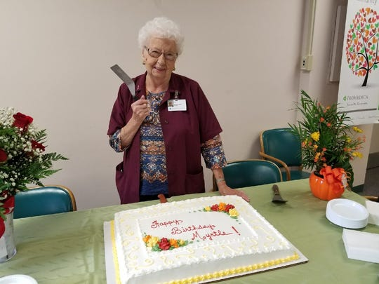 Myrtle Koch gets ready to cut her vanilla and spice cake celebrating her 100th birthday.