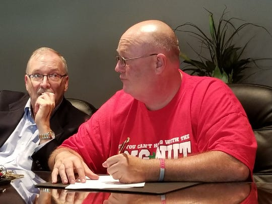 """Jon """"Big Nut"""" Peters, with attorney Jim Ellis, signs a document to establish his new Ohio State University scholarship."""