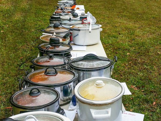 A crockpot potluck is laid out for an open-air buffet.