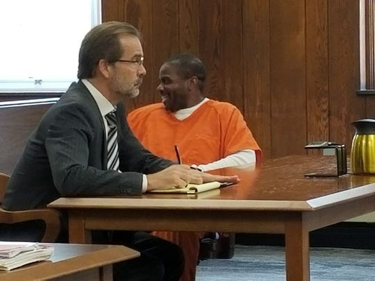 Prior to being sentenced to 34 years in prison, Keith Nettles smiles, waves and blows kisses to friends and family in the courtroom in November 2017. His attorney David Klucas is at left.
