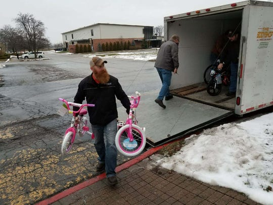 Jason Gibson carries in two bikes to be donated to