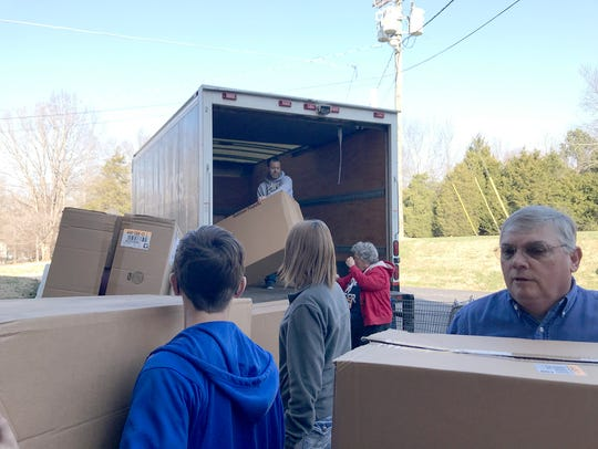 Volunteers help unload toys and gift at First Baptist