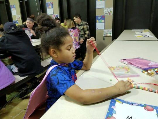 First grader JaKari Bradley makes a Fruit Loop necklace.