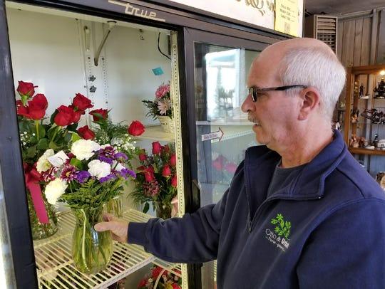 Floral designer Rick Heimbaugh selects a floral arraignment