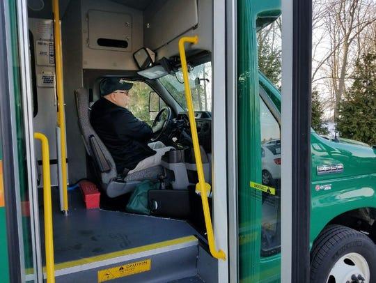 TRIPS driver Bill Voelker opens the door to let passengers
