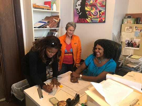 Chrishaunda Lee Perez (left) writes a check to support