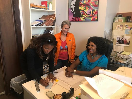 Chrishaunda Lee Perez (left) writes a check to support the work of Belinda Pittman-McGee, founder of Milwaukee's Nia Imani shelter. Looking on is Julily Kohler, who chairs the Nia Imani board.