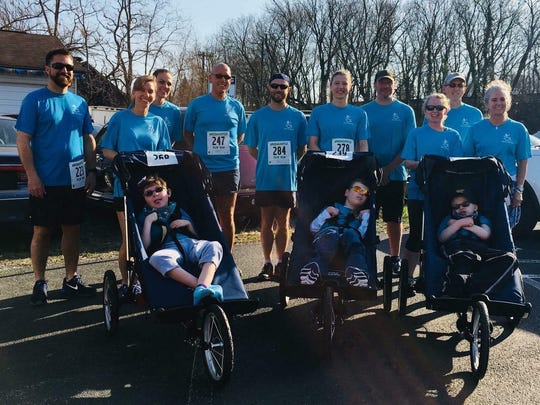 Runners representing Kids in Motion pose for a photo before last weekend's Greencastle Pub Run. Kids in Motion pairs experienced runners with special needs children to compete in local races.