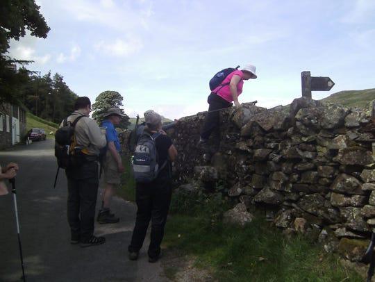 Clamber over stiles to surmount rock wall boundaries.