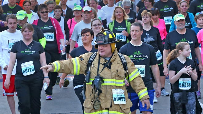 Joseph Tunny, from Danville IN, wears his firefighter gear as he starts the Finish Line 500 Festival 5K race, Saturday, May 2, 2015.