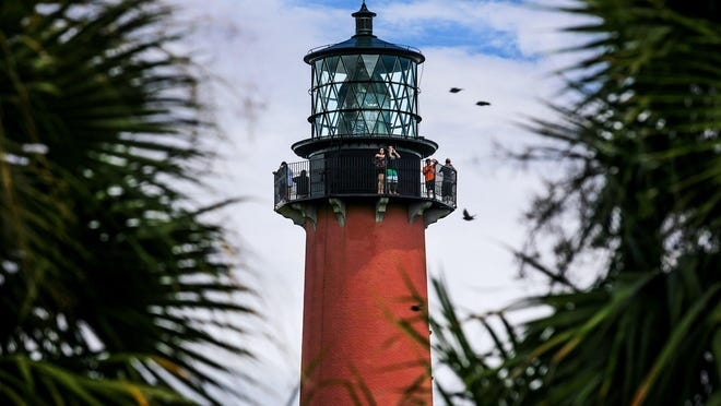 Visitors stand atop the Jupiter Inlet Lighthouse during a guided tour, August 22, 2017, in Jupiter, Florida.
