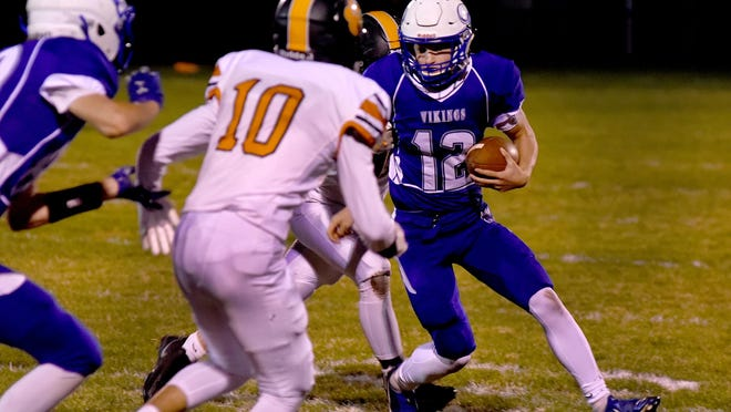 Dundee quarterback Carson Irwin carries the ball as Ambrose Horwath (1) moves in to make a tackle for Hudson during a 21-7 Hudson win Friday night.