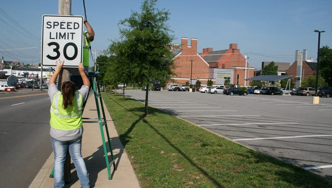 Clarksville Street Department workers Joe Reeves and Brandi Singleton were busy  Wednesday morning installing new speed limit signs on College Street near APSU.
