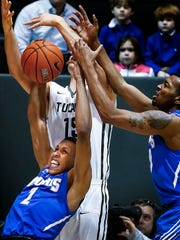 University of Memphis forward Jimario Rivers (left) grabs a rebound away from Tulane University forward Ryan Smith (back) as teammate K.J. Lawson (right) helps on the play during first-half action at Fogelman Arena in Devlin Fieldhouse in New Orleans, La.