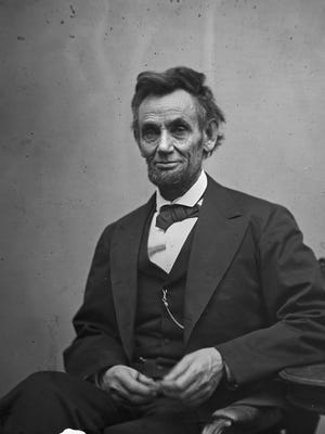 President Abraham Lincoln, seated and holding his spectacles and a pencil on Feb. 5, 1865.