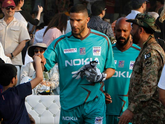 England soccer star David James, center, touches fists with a young boy while he along with French player Nicolas Anelka, second right, arrive to play an exhibition soccer match in Lahore, Pakistan, Sunday, July 9, 2017. Former Manchester United and Wales winger Ryan Giggs said he was impressed with Pakistan youngsters' love for soccer after seven iconic footballers, also including Ronaldinho, featured in a rare two-game exhibition series in the country. (AP Photo/K.M. Chaudary)