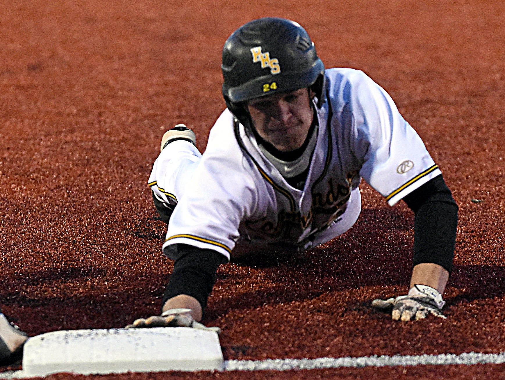Hendersonville High senior Aris Welden slides safely back into first base during the first inning.