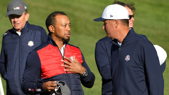 "Team USA vice captain Tiger Woods talks with ""Bones"" caddie Jim Mackay at Hazeltine National Golf Club ahead of the 41st Ryder Cup."