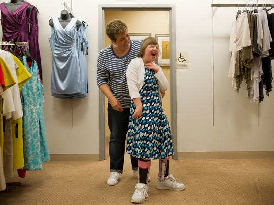 Keri Hartz, of Evansville, stands with her daughter, Kenzie Hartz, 15, also of Evansville, as she tries on dresses in preparation for A Night of Stars & Styles fashion show at Dillard's in Evansville.