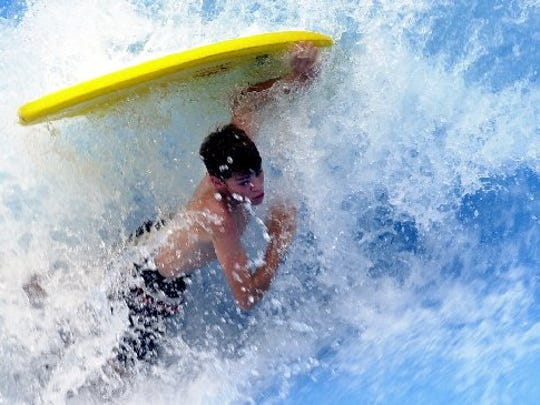 """A boarder wipes out while riding """"The Wave"""" at Water World in Denver Friday August 2, 2002."""