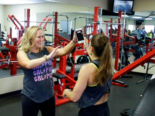 In this Saturday, Feb. 18, 2017 photo, Associated Press writer Jenna Fryer, left, high-fives Danica Patrick after a workout at Daytona International Speedway, in Daytona Beach, Fla. Patrick is really serious about health and clean eating, and as her driving days may be nearing an expiration date, a second career in lifestyle and fitness could be up next.