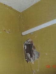 A large hole in a wall can be seen in a home owned