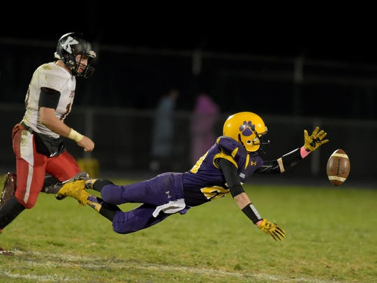 Hagerstown's David Castle dives but can't come up with a catch against Knightstown's Tyler Burton during a football sectional game Friday, Oct. 28, 2016 in Hagerstown.