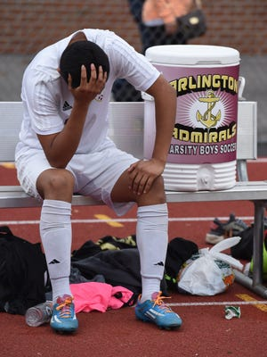 Arlington's George Pogyo holds his head after his team was eliminated in penalty kicks by Ithaca during the Class AA regional final in Shrub Oak on Saturday.