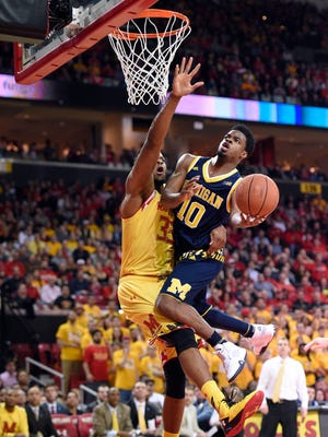 Michigan guard Derrick Walton Jr. (10) goes to the basket as he is fouled by Maryland forward Damonte Dodd (35) during the first half of an NCAA college basketball game, Sunday, Feb. 21, 2016, in College Park, Md.
