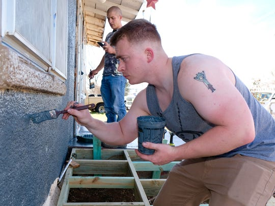 Airman 1st Class Donovan Lavender paints an elderly woman's house while volunteering with the Dyess We Care Team.